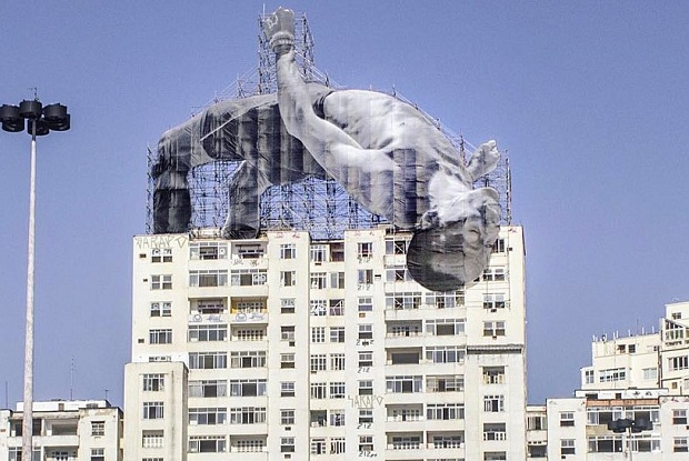 One of French artist JR's larger-than-life athletes looms--er, leaps--over the Rio skyline. Image c/o JR-net.art and The Art Newspaper.
