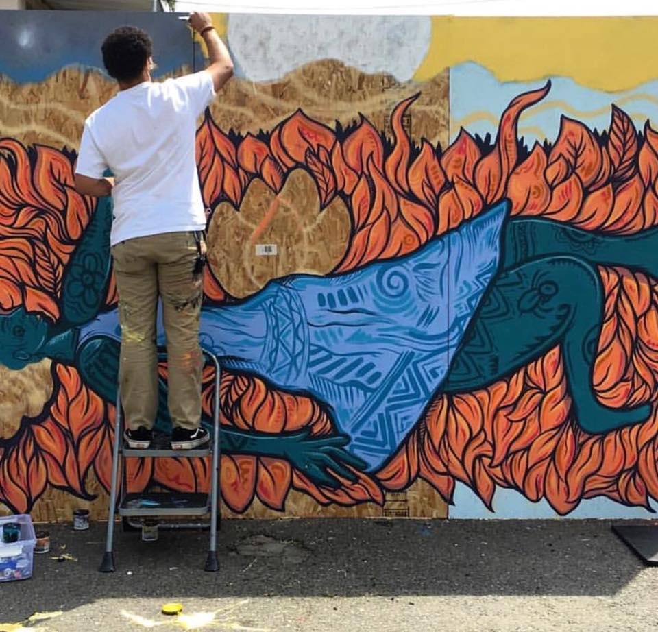 Aik Brown creates a mural, c/o Wide Open Walls Facebook