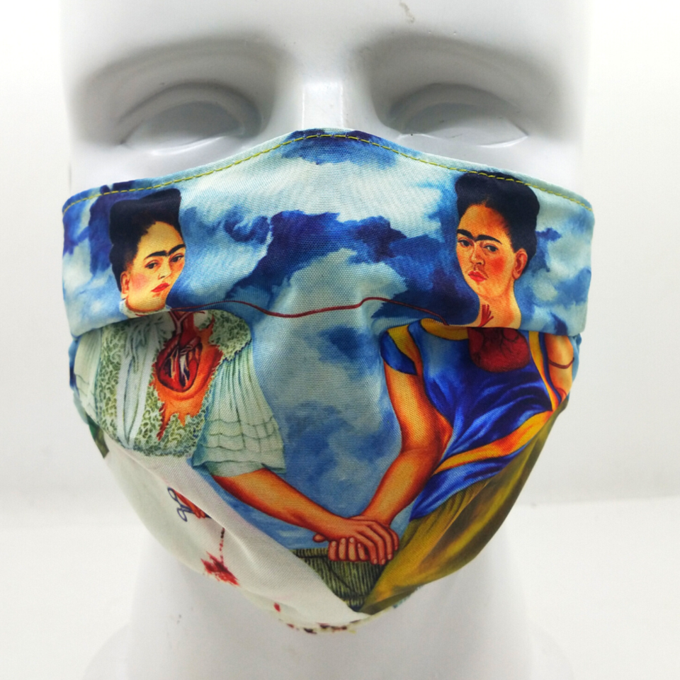 A face mask with a print from Frida Kahlo's Two Fridas painting, featuring two versions of the artist connected by a vein.